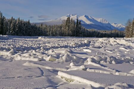 Winter Scenery on sunny winter day with frozen River an Hudson Bay Mountain in back.