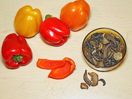 Food preparation, Bell Peppers vegetables and Bowl with dried mushrooms on wooden Board.