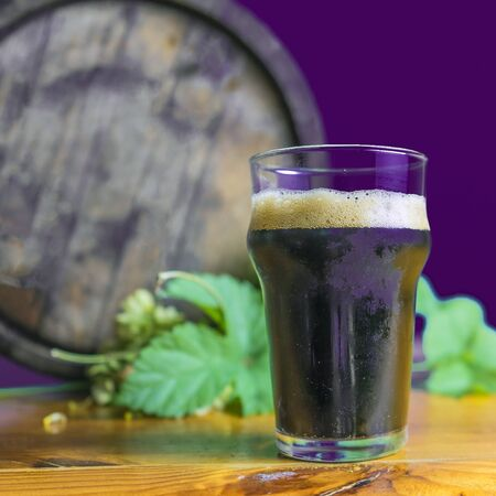 dark beer glass on the table with hops on the background of barrels. Purple backgraund. Banque d'images