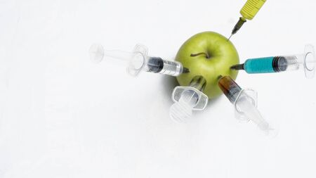 Pesticides, nitrates, gmo and other chemicals are injected into a green apple with syringes. Archivio Fotografico