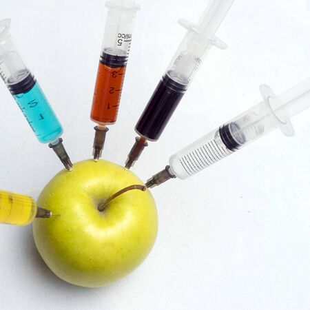 nitrates, pesticides, fungicides and other chemicals are injected into a green apple with a syringe. Nearby is a magnifying glass. The concept of GMO and genetically modified organism. Non-GMO and natural fruits without chemical additives.
