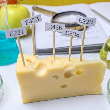 Aditivos alimentarios nocivos. En el queso hay carteles con el código E-suplementos. Siguiente Sobre la mesa hay frascos y un cuaderno con notas. De cerca.