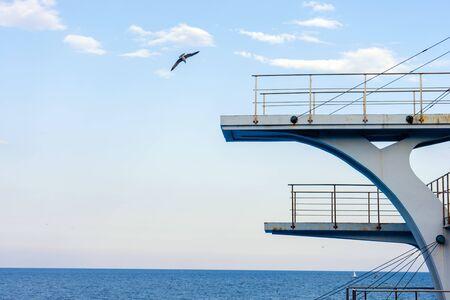 Trampolín o torre blanca contra un cielo azul claro. Al fondo el mar