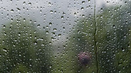 Raindrops on the window with blurred background of cable car in the rainy day Stock Photo