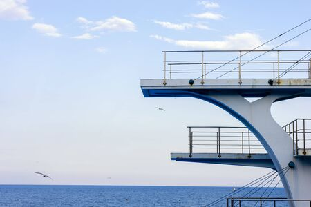 White diving board or tower against a clear blue sky. In the background the sea