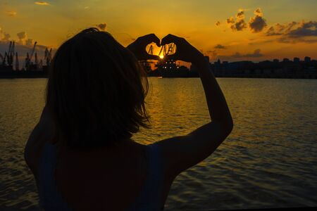 Woman making heart with hands in sunset. Love symbol in sunny summer night.