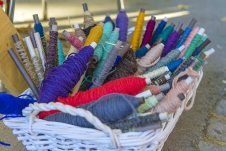 Tools for a loom in a basket: cotton yarn dyed in natural colors, shuttle, ball of thread. Close-up.
