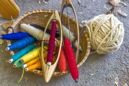 Tools for a loom in a basket: cotton yarn dyed in natural colors, shuttle, ball of thread. Close-up Imagens