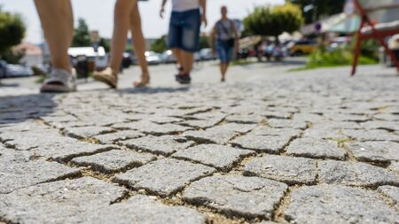 People cross the street, an old pavement close-up. Summer is a sunny day Imagens