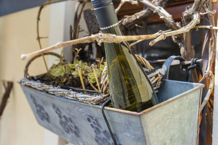Green wine bottle in a basket with plants on the street, background, decor