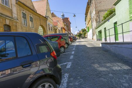 Many cars are parked along the streets of the old city
