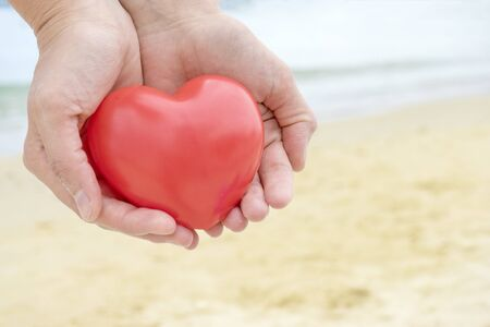 Red fabric heart lay on palm of hand with sea on background. Valentine day.