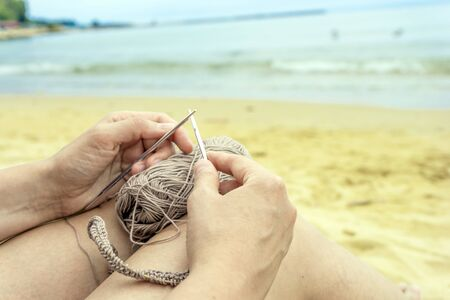 woman knits grey yarn openwork pattern with metal knittings on beach.