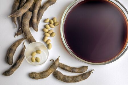 Soya beans with soya sauce on a white table. Top view.
