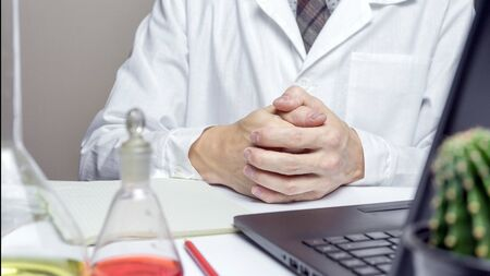 Close up of male doctor or medical student in lab holding hands on desk. health and education concepts.