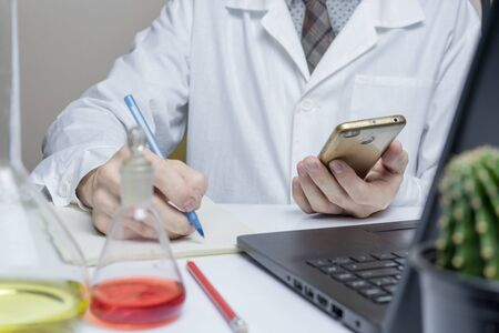 Male doctor or medical student using mobile smart phone working in lab, Close up