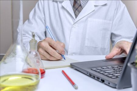 Close up male doctor or medical student in laboratory, making notes in notepad. health and education concepts.