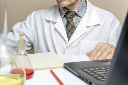 Close up male doctor or medical student in lab, electronic records system.