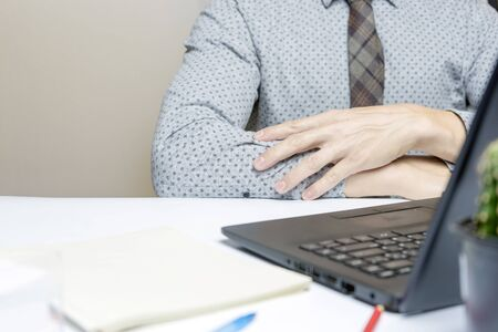 Man in shirt and tie, holding hands on desk. Close up. Stock Photo