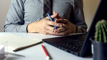 Close up man shirt and tie, holding hands on a table next to a notebook and laptop Stock Photo