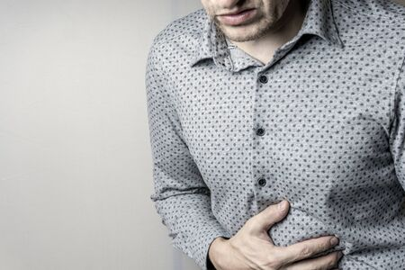 a man having abdominal pain on a grey background. Stock Photo