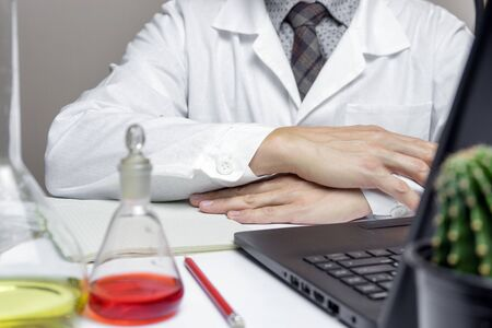 Male doctor or medical student in lab holding hands on desk. Close up.