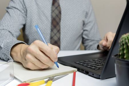 A business man works on a laptop, making notes in a notebook. close-up.
