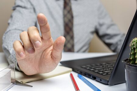 Businessman shows his hand with index finger. Close up.
