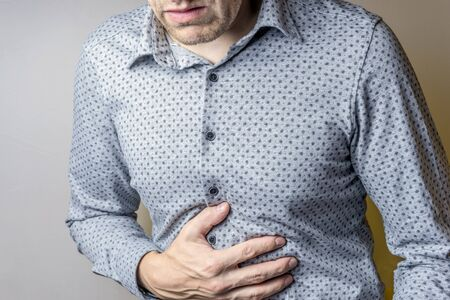 a person having abdominal pain on a grey background. Stock Photo
