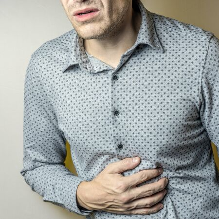 a man having abdominal pain on a grey background. 写真素材
