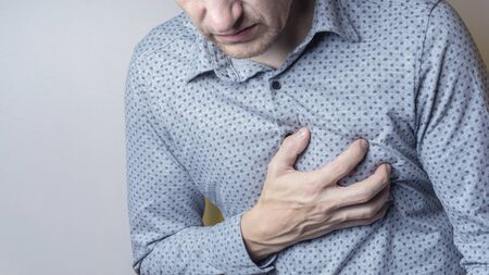 Man suffering from severe sharp heartache, chest pain. Heart disease concept 스톡 콘텐츠