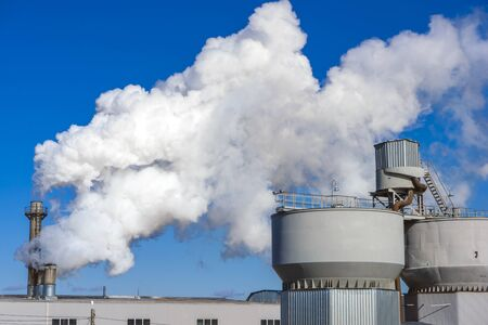 Smoking pipes of thermal power plant against blue sky on sunset.