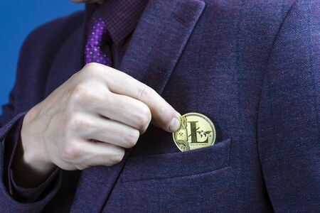 Businessman placing a Bitcoin in his jacket pocket in a close up view on his fingers and the coin.