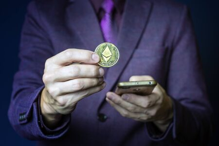 Businessman in purple suit is holding golden ethereum coin between fingers, smart contract crypto currency sign