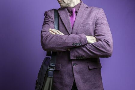 Business fashion man wearing purple suit with tie and bag on his shoulder. Studio shot against blue.