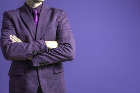 Close up of a businessman in a purple suit confidently on a dark blue background Stock Photo