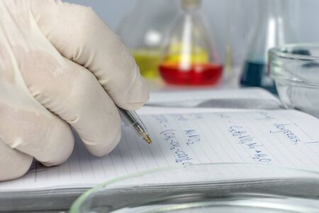 Food safety laboratory, scientist concept. Inspector writing test note on notebook after doing research in lab. Close up 写真素材