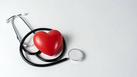 stethoscope on white background with plush heart top view.