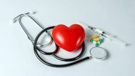 Medical equipment : stethoscope pills and syringe on white background.