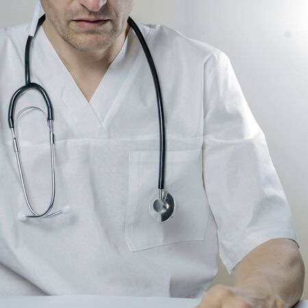 Medical doctor on white background holding a stethoscope.