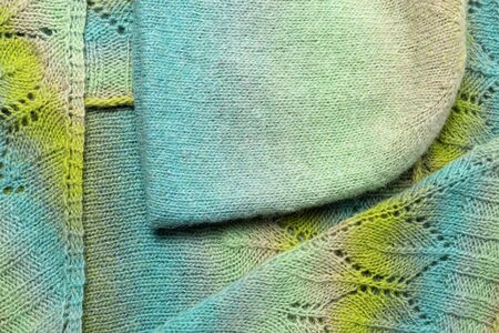 Colorful woolen background for winter time. Scarf and hat. View top.