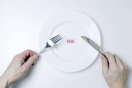 Foto Schadelijke levensmiddelenadditieven. Mannenhanden houden een mes en een vork vast. Op het plaatje staat een plaatje met de E-additief code.