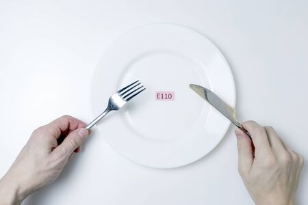 Photo Harmful food additives. Men's hands hold a knife and a fork. On the plate is a plate with the E-additive code.
