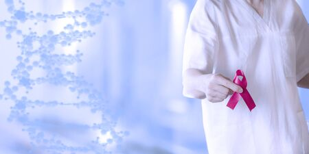 doctor in white uniform holds a red ribbon-symbol of the fight against disease AIDS and vasculitis, close up Stock Photo