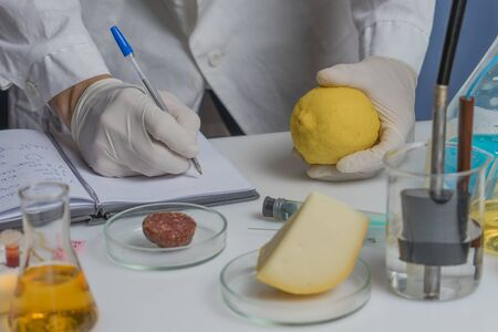 Laboratory assistant at the workplace makes notes in a notebook. Laboratory procedure for food safety, analysis of food products from the market.
