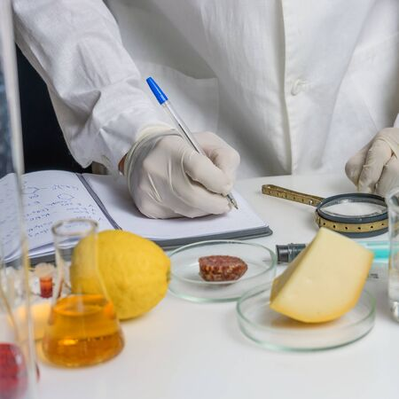 Laboratory assistant at the workplace. Laboratory procedure for food safety, analysis of food products from the market. There are signs in the cheese with the code of the E-application.