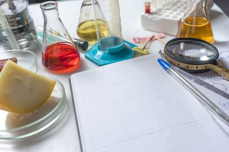 Photo Notepad, tablets with additives E, test tubes and laboratory equipment. Food laboratory. Close up on a white table.