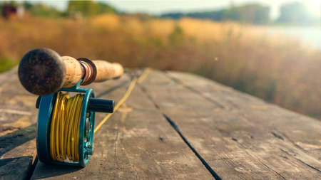Fly fishing rod with on wood background. Autumn sunny day. Autumn sunny day.