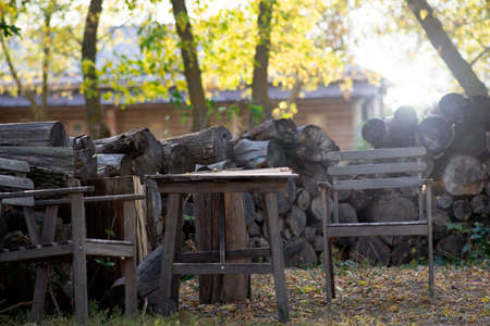 wooden table and chairs in the backyard, firewood background. Autumn sunny day.