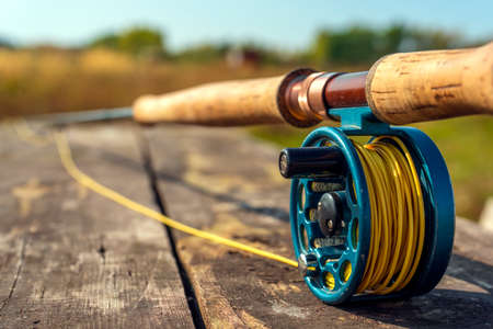 Flyfishing rod and reel with lake and mountians in the background. Autumn sunny day.